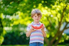 吃西瓜的小学龄前孩子男孩在夏天 免版税库存照片