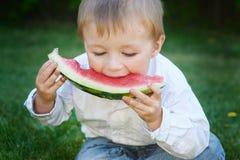 吃西瓜的小男孩在夏天庭院里 免版税库存图片