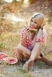 吃西瓜的少妇户外 免版税库存照片