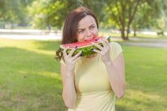 吃西瓜的微笑的少妇 库存图片