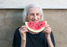 吃西瓜的快乐的祖母在后院 免版税库存照片