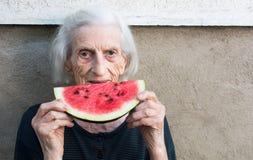 吃西瓜的快乐的祖母在后院 免版税库存图片