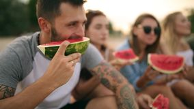 吃西瓜的愉快的朋友坐沙滩在度假 年轻穿着蓝色牛仔裤短裤的人和妇女 股票录像