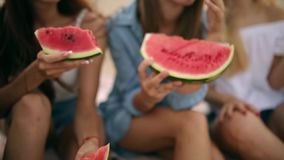 吃西瓜的愉快的朋友坐沙滩在度假 年轻穿着蓝色牛仔裤短裤的人和妇女 股票视频