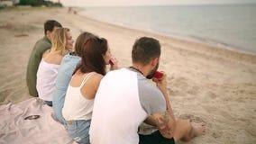 吃西瓜的愉快的朋友坐沙滩在度假 年轻穿着蓝色牛仔裤短裤的人和妇女 影视素材