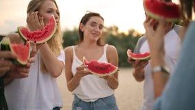 吃西瓜的愉快的朋友站立在沙滩和聊天 年轻穿着蓝色牛仔裤短裤的人和妇女近 股票视频