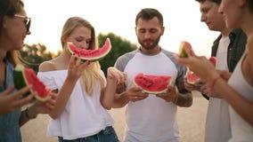 吃西瓜的愉快的朋友站立在沙滩和聊天 年轻穿着蓝色牛仔裤短裤的人和妇女近 股票录像