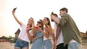 吃西瓜的朋友站立在沙滩和采取与智能手机照相机的selfies 年轻人和妇女佩带 股票录像