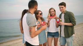 吃西瓜的朋友站立在沙滩和采取与智能手机照相机的selfies 年轻人和妇女佩带 股票视频