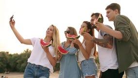吃西瓜的朋友站立在沙滩和采取与智能手机照相机的selfies 年轻人和妇女佩带 影视素材