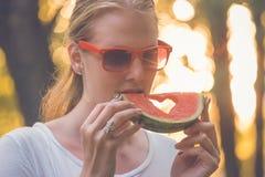 吃西瓜的美丽的妇女户外 免版税库存图片