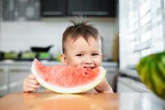 吃西瓜的逗人喜爱的小男孩在厨房里 免版税库存照片