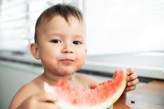吃西瓜的逗人喜爱的小男孩在厨房里 库存图片