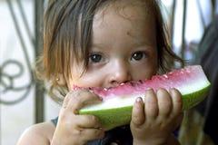吃西瓜的画象拉丁美州的小女孩 图库摄影