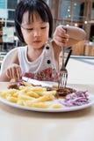 吃西部食物的亚裔矮小的中国女孩 库存图片