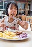 吃西部食物的亚裔矮小的中国女孩 免版税库存图片