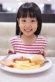 吃西部食物的亚裔矮小的中国女孩 库存照片
