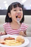 吃西部食物的亚裔矮小的中国女孩 免版税图库摄影