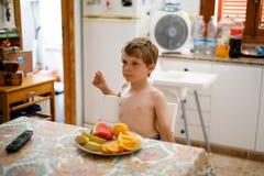 吃许多不同的果子的逗人喜爱的小孩男孩在家庭厨房里在夏天 免版税库存图片