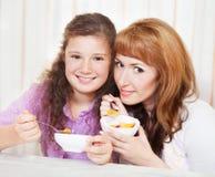 吃谷物和果子的母亲和女儿 免版税库存照片