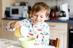 吃谷物和牛奶早餐或午餐的愉快的矮小的白肤金发的孩子男孩 库存照片