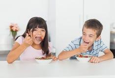 吃谷物早餐的兄弟姐妹在厨房里 库存图片