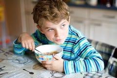 吃谷物用牛奶和莓果的可爱的矮小的白肤金发的学校孩子男孩早餐或午餐的 免版税库存照片