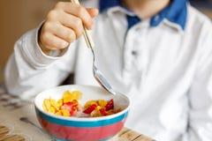 吃谷物用牛奶和莓果,新鲜的草莓的一点白肤金发的学校孩子男孩早餐 免版税图库摄影