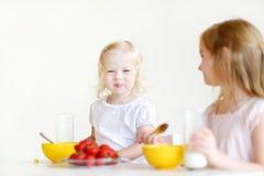 吃谷物的两个逗人喜爱的妹在厨房里 免版税库存照片
