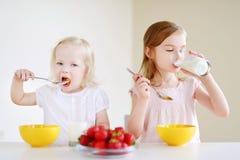 吃谷物的两个逗人喜爱的妹在厨房里 库存照片