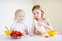 吃谷物的两个逗人喜爱的妹在厨房里 免版税图库摄影