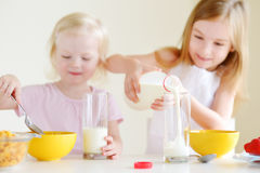 吃谷物的两个逗人喜爱的妹在厨房里 库存图片