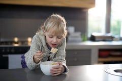 吃谷物的小女孩敲响与从碗的匙子 免版税库存图片