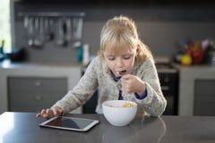 吃谷物的小女孩敲响与从碗的匙子 免版税库存照片