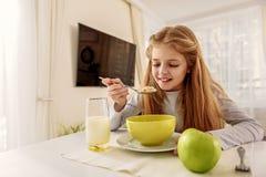 吃谷物的愉快的女孩在厨房里 免版税库存图片