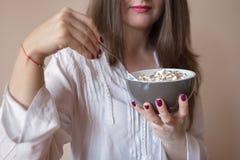 吃谷物的美丽的少妇 免版税库存照片