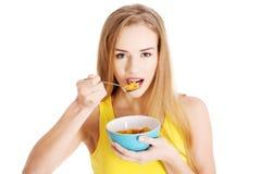 吃谷物的美丽的白种人妇女。 库存图片