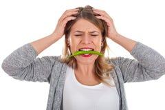 吃辣椒辣椒粉的美丽的妇女 免版税库存图片