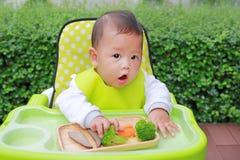 吃通过婴孩被带领的断绝BLW的亚裔婴儿男婴 手抓食物概念 库存图片