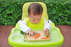 吃通过婴孩被带领的断绝BLW的亚裔婴儿男婴 手抓食物概念 免版税图库摄影