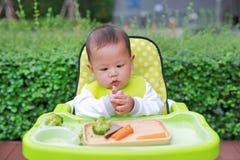 吃通过婴孩被带领的断绝BLW的亚裔婴儿男婴 手抓食物概念 图库摄影