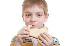 吃部分的男孩面包 免版税库存图片