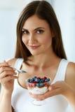 吃酸奶、莓果和谷物的美丽的妇女 健康的饮食 免版税库存图片