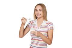 吃酸奶和微笑的女孩 免版税图库摄影