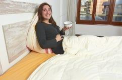 吃酸奶用在床上的草莓的愉快的妇女 库存图片