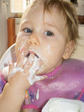 吃酸奶用她的手的婴孩 库存图片