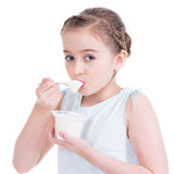 吃酸奶的一个小女孩的画象。 免版税库存图片