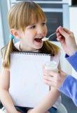 吃酸奶的一个少妇和小女孩在厨房里 免版税库存照片