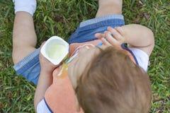 吃酸奶的两岁的男孩坐草 免版税库存图片