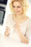 吃酸奶的愉快的妇女 免版税图库摄影